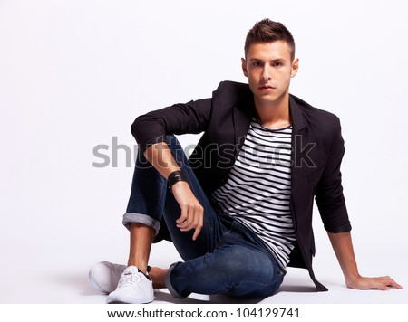 young fashion man looking down and standing with his hands in pockets on white background with hard shadow