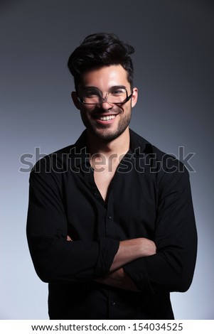 young fashion man posing with his eyeglasses upside down and smiling while holding hands crossed. isolated on a gray background