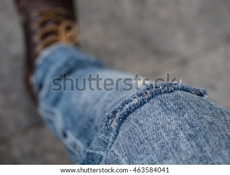 Young fashion man's legs in jeans and boots