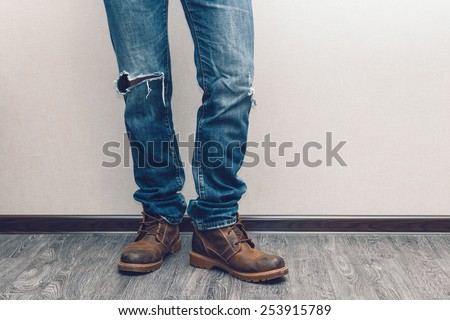 Young fashion man's legs in jeans and boots on wooden floor - stock photo