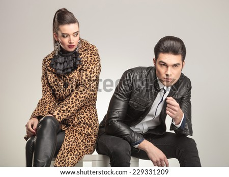 Young fashion man sitting and thinking while looking away. His girlfriend is sitting near looking at thim.