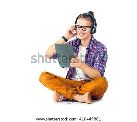 Young fashion man sitting on the floor and enjoying music with his headphones. Handsome young stylish hipster guy in headphones holding tablet pc and listening music, isolated on a white background - stock photo