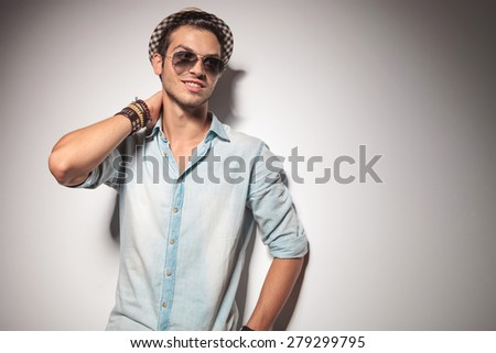 Young fashion man smiling and looking away while holding one hand to his neck. - stock photo