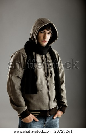 Young fashion man standing against a grey background - stock photo
