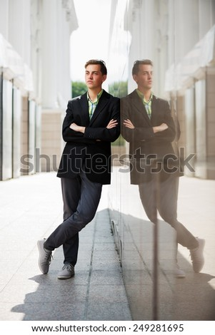 Young fashion man standing against the wall - stock photo