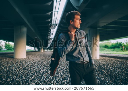 Young fashion man standing under a bridge - stock photo
