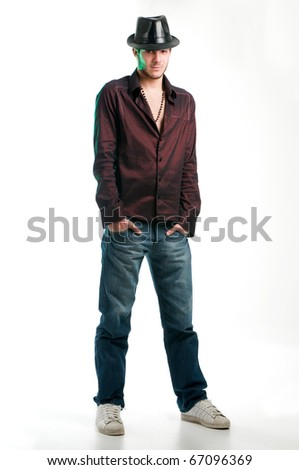 Young fashion man standing with arms in pocket, on white, studio shot