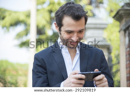 young fashion man walking in the city street and texting with smartphone - stock photo