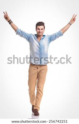 Young fashion man walking on white studio background holding both hands in the air while showing the victory sign. - stock photo