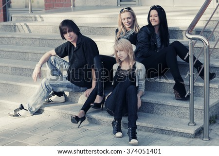 Young fashion men and women sitting on the steps  - stock photo