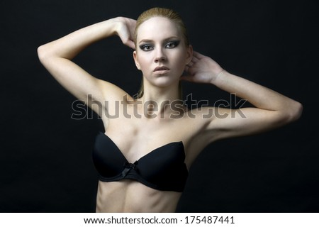 young fashion model blond hair wearing black bra against black background - stock photo