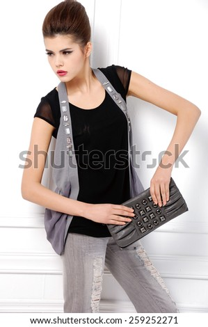 young fashion model  holding purse posing in studio - stock photo