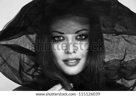 Young fashion model in black veil close-up studio portrait - stock photo