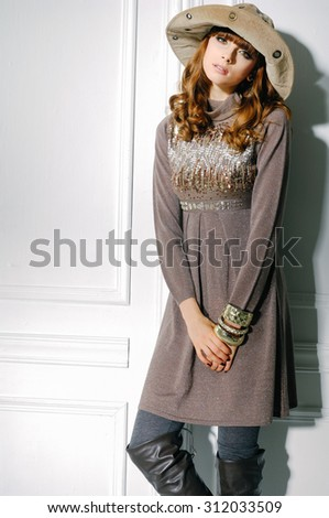 young fashion model in boots with hat posing in studio - stock photo