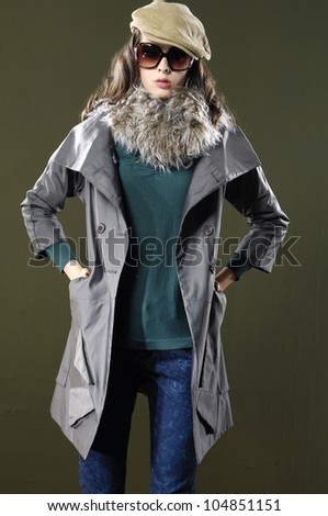 young fashion model in coat with hat posing - stock photo