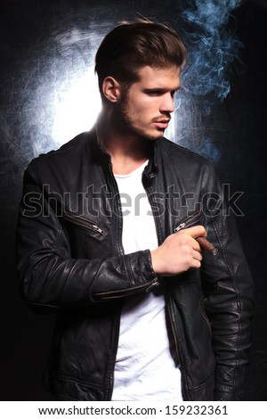 young fashion model in leather jacket smoking a big cigar and looking away from the camera - stock photo