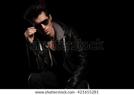 young fashion model in leather jacket taking off his sunglasses on black studio background