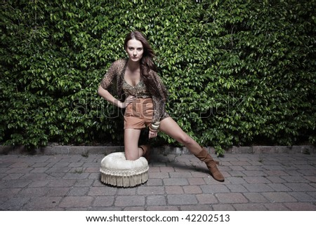 Young fashion model kneeling on a plush stool - stock photo