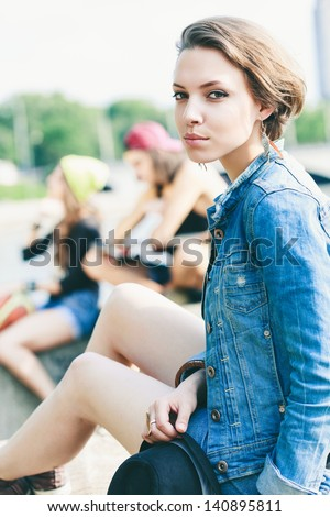 Young fashion model posing in jeans jacket with hat. Outdoors, lifestyle - stock photo