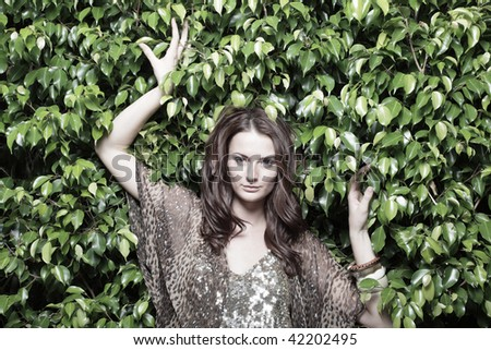 Young fashion model posing on a nature background - stock photo