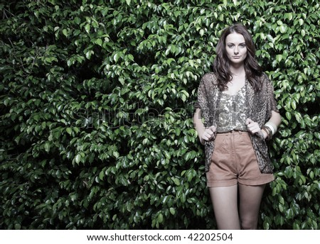 Young fashion model posing on a nature background