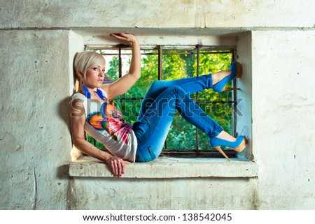 young fashion model woman lie in window