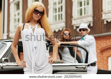 Young fashion people at the retro car - stock photo