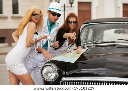 Young fashion people with a road map at the retro car  - stock photo