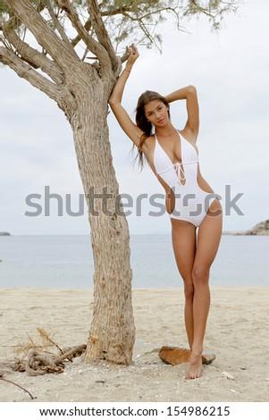 young fashion pretty brunette sexy woman in white bikini on the beach - stock photo