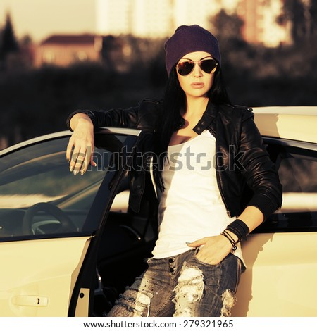 Young fashion punk woman by her car - stock photo