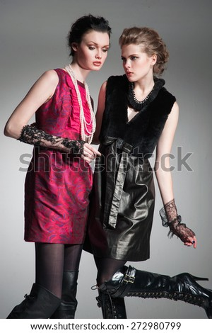 Young fashion two girl wearing black and red clothes on gray background  - stock photo