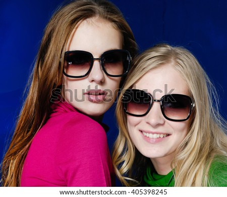 young fashion two model with sunglasses-blue background
