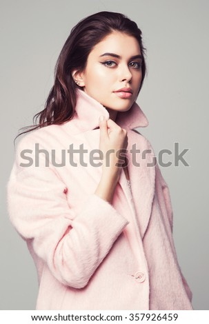 young fashion woman beauty portrait posing in studio wearing in pink coat - stock photo