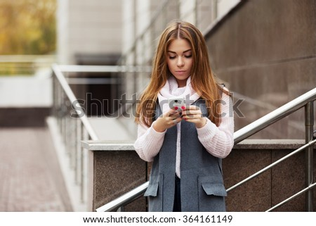 Young fashion woman calling on cell phone on city street - stock photo