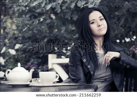 Young fashion woman drinking tea at sidewalk cafe