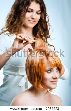 Young fashion woman hairdresser makes hairstyle for a girl isolated on white background - stock photo