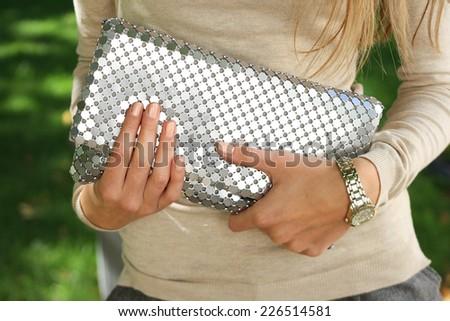 young fashion woman hold silver handbag clutch . stylish accessory young woman hold silver handbag clutch . stylish accessory - stock photo