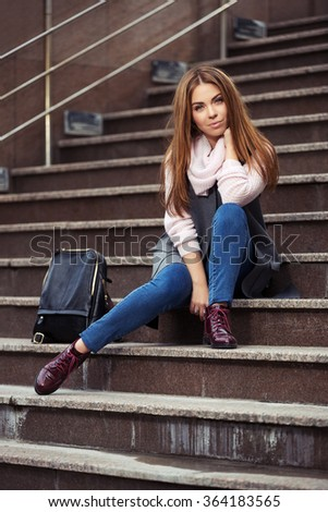 Young fashion woman in grey coat with handbag sitting on the steps - stock photo