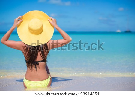 Young fashion woman in hat on the beach - stock photo