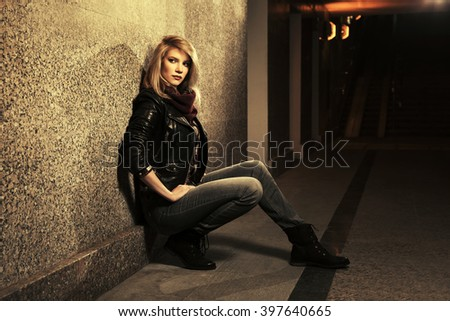 Young fashion woman in leather jacket sitting at the wall - stock photo