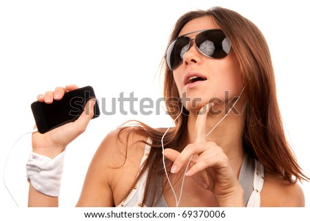Young fashion woman in sunglasses enjoy listening to music in white earphones isolated on a white background - stock photo
