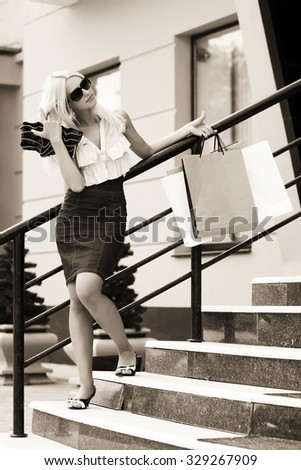 Young fashion woman in sunglasses with shopping bags at the mall - stock photo