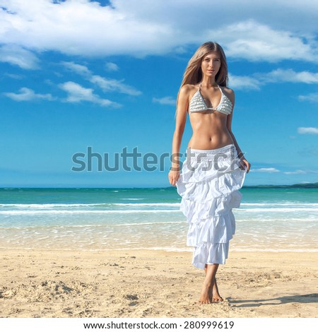 Young fashion woman posing at tropical beach