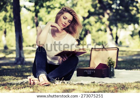 Young fashion woman reading a book in city park - stock photo