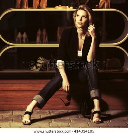 Young fashion woman sitting on the mall window. Female stylish model on night city street - stock photo