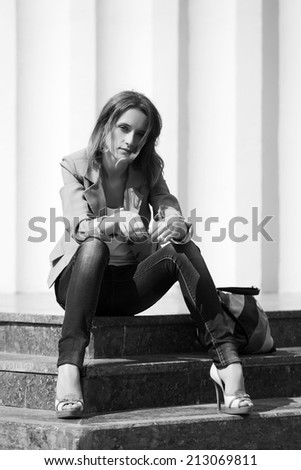 Young fashion woman sitting on the steps - stock photo