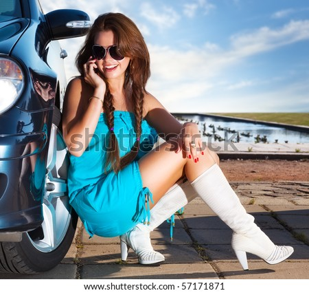 Young fashion woman talking on phone at her car. - stock photo