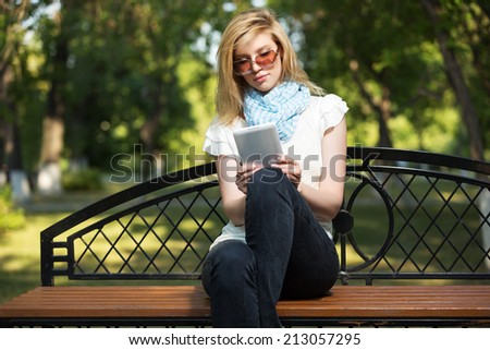 Young fashion woman using tablet computer in a city park - stock photo
