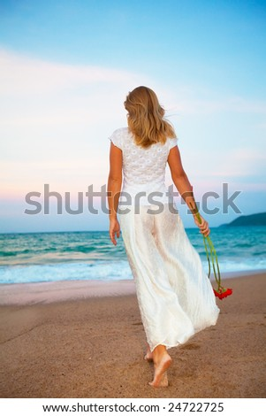 Young fashion woman walking with flowers on the  beach - stock photo