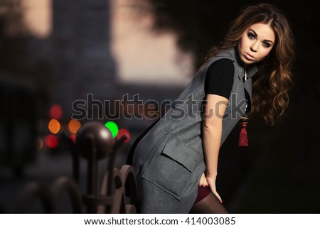 Young fashion woman with long curly hairs on night city street. Female model in grey coat outdoor - stock photo